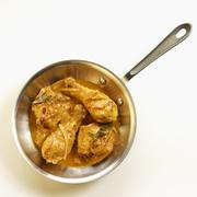 Chicken bit in a red curry sauce in a pan Stock Photos