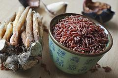 An arrangement of fingerroot and a bowl of red rice (Thailand) Stock Photos