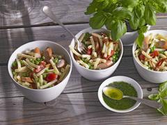 Pasta salad with peas, tomatoes and sausages Stock Photos