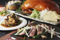 A Chinese buffet featuring grilled beef, Peking duck and prawns with vegetables Stock Photos