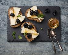 Bruschetta topped with cheese and blackberries Stock Photos