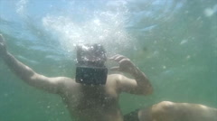 Underwater VR guy looks around, smiling under the waves Stock Footage