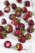 Fresh strawberries scattered on white wooden surface Stock Photos