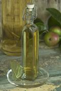 A bottle of apple vinegar and apples in a rustic cupboard niche Stock Photos