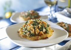 A potato fritter topped with salmon and spinach Stock Photos