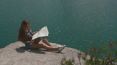 Young active backpacker girl rests on mountain rock upon large water surface of Stock Footage