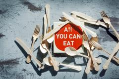 An 'All you can eat' sign surrounded by cutlery Stock Photos