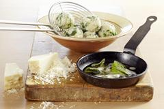 Spinach dumplings with sage butter and Parmesan cheese Stock Photos