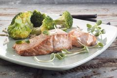 Salmon fillet with broccoli florets and sunflower shoots Stock Photos