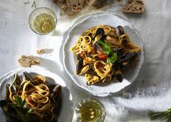 Spaghetti with mussels, white wine and bread (seen from above) Stock Photos