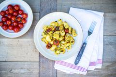 Pasta with fried cherry tomatoes and basil Stock Photos