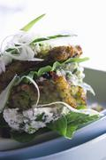 Courgette fritters with goat's cheese, ricotta, spinach and cucumber slices Stock Photos