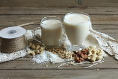 Two glasses of vegan milk, nuts, soya beans and oats Stock Photos