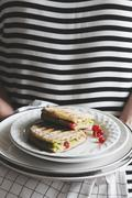 A woman serving a panini with avocado and redcurrants Stock Photos