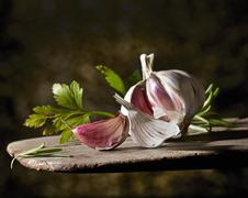 A garlic bulb and flat-leaf parsley on a wooden board Stock Photos