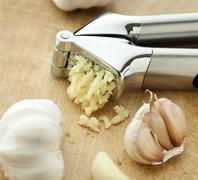 A garlic crusher and garlic Stock Photos