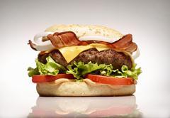 A bacon cheeseburger on a white surface Stock Photos