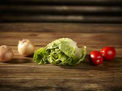Cos lettuce, tomatoes and onions on a wooden surface Stock Photos