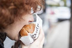 A red-haired teenager biting into a hamburger Stock Photos