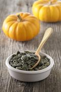 A dish of pumpkin seeds with a spoon Stock Photos