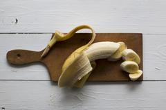 A banana on a wooden chopping board Stock Photos