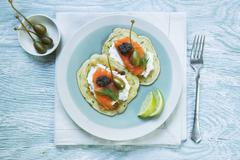 Courgette cakes with smoked salmon, crème fraîche, capers and tapenade Stock Photos