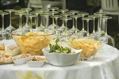 An aperitif buffet with wine glasses, crisps, olives and peanuts Stock Photos