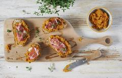 Open sandwiches topped with Parma ham, sweet potato paste and thyme Stock Photos