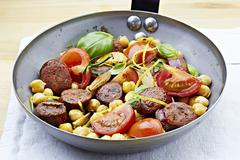 Fried chorizo chickpea with tomatoes and basil Stock Photos