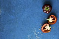 Dark red mini peppers, whole and halved, on a blue surface Stock Photos