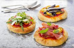 Three mini pizzas with different toppings Stock Photos