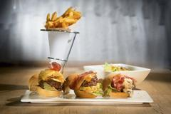 Three mini burgers on a serving platter with a cone of chips in the background Stock Photos