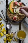 Honey being drizzled over roasted wholemeal oats in a cast-iron pan with fresh Stock Photos