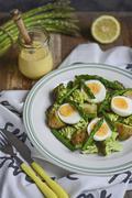 Asparagus salad with potatoes, broccoli, hard-boiled eggs and sauce Hollandaise Stock Photos