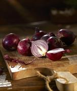 Red onions on a wooden chopping board Stock Photos