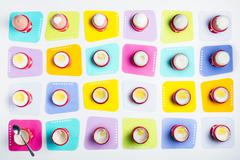 Boiled eggs in egg cups on coloured coasters (seen from above) Stock Photos