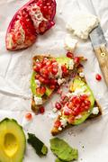 Wholemeal bread triangles with avocado, feta cheese and pomegranate seeds Stock Photos