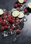 Raspberries, limes and ice cubes Stock Photos