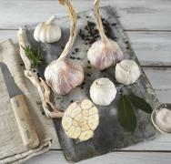 Garlic (purple and white) and bay leaves on a wooden board Stock Photos