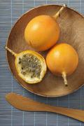 Yellow passion fruits, whole and halved, on a wooden plate Stock Photos