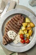 Grilled steak with a pepper sauce and fried potatoes Stock Photos