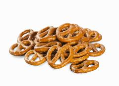 A pile of mini salted pretzels on a white surface Stock Photos