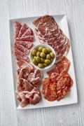 An Italian antipasti platter with ham, salami and olives Stock Photos