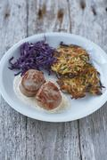 Pork medallions with a creamy mustard sauce served with a potato and apple cakes Stock Photos
