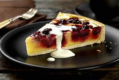 A slice of cherry and vanilla pudding tart with cream Stock Photos