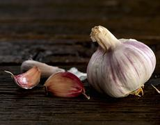 A bulb of garlic and some garlic cloves on a wooden surface Stock Photos