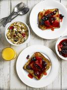 Spicy berries toast, muesli and orange juice for breakfast Stock Photos