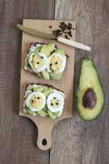 Slices of bread topped with avocado, egg and peppercorns Stock Photos