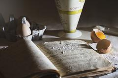A baking scene with and old recipe book, eggs and flour Stock Photos