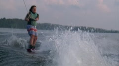 Girl rides the waves on wakeboard6 summer sunset on pond Stock Footage